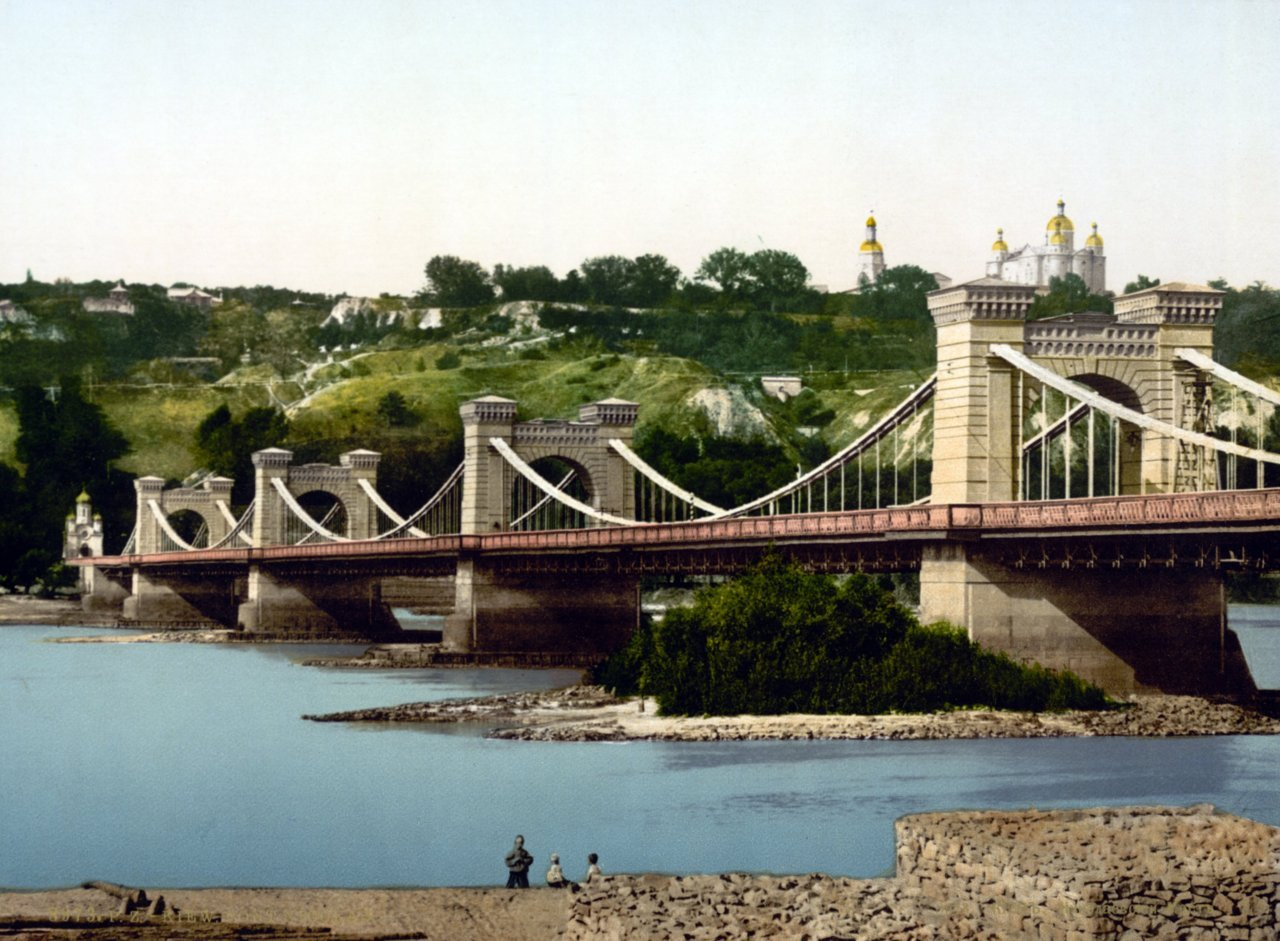 Nicolay's Chain Bridge ,Kiev  1900 The Nicholas Chain Bridge (or Nikolaevsky Chain Bridge; Ukrainian: Миколаївський ланцюговий міст; Russian: Николаевский цепной мост) was a bridge over the Dnieper that existed from 1855 to 1920 in Kiev. The bridge was designed by Irish engineer Charles Blacker Vignoles. Construction started in 1848 and was completed in 1855. The 776 m long bridge was the largest at that time in Europe. In 1920, during the Polish-Soviet War, the bridge was blown up by retreating Polish troops. It was restored based on old drawings by Evgeny Paton and opened again in 1925 under the name Yevgenia Bosch Bridge. Paton had significantly changed its structure and raised it by  several metres, so that the Yevgenia Bosch Bridge may be considered as a  new bridge. On 19 September 1941 Yevgenia Bosch Bridge was demolished by  retreating Soviet troops and was never restored after the war. In 1965  in place of the former chain bridge a new Kiev Metro Bridge was built.