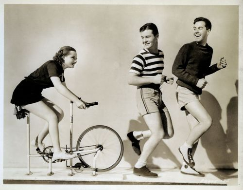 Eleanore Whitney chases on a bike. Tom Brown and Johnny Downs try to escape.