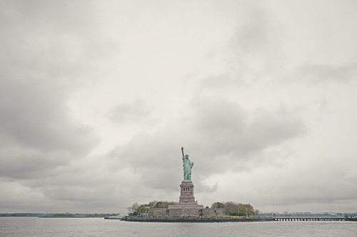 "lady liberty // nyc, ny // canon 5d mkii so many times we see places in photos, and we wonder what it feels like to be there, and when we go there, we feel it necessary to photograph it. when i saw the statue in person i was like ""wow… the history here…"" and it didn't occur to me to take a photograph of it… so i grabbed a shot on our boat off that rock to remember what it was like to see the statue in person."