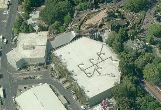 seizethefuture:  Aerial view of the Haunted Mansion and Splash Mountain show buildings  Also shown: my old stomping grounds, the ODV (Outdoor Vending) warehouse! This is where the food carts and stock are kept when they aren't in the park. On the north side of the building (this photo looks more or less south to north), you can see the tuggers and trailers used to tow wagons to and from the nearest onstage entrance, so the carts don't have to be pushed up that giant hill in Critter Country anymore. Because once a guest gets in the way on the way up that hill, good luck getting the cart moving uphill again after you've stopped to avoid killing them. And downhill? Good luck stopping at all if someone gets in your way when you're trying to hold back a couple thousand pounds on wheels that wants to careen down the hill. Hence, the large carts now being driven around the outside of the park. It's more expensive, but exponentially safer. Here's a dumbed-down version of the picture: