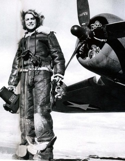 early female pilot has the clothes to match her job.  Shearling bomber jacket and all.