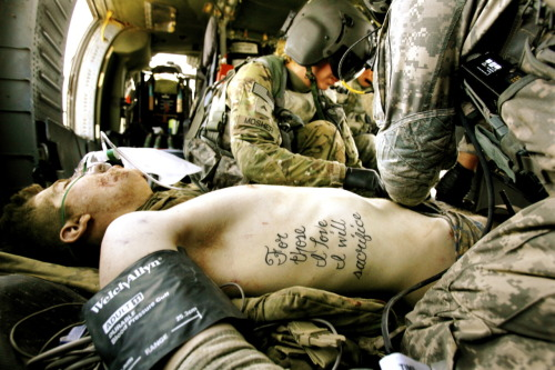 "agoldenrendezvous:  Tattoos are as old as war. Lots of soldiers get them, with military motifs, girlfriend's names, or various guns, skulls or dragons adorning their skin. Some get something less ornate. Private First Class Kyle Hockenberry had For those I love I will sacrifice stitched into his flesh. He had no idea how prescient he was.   A member of the 1st Infantry Division, Hockenberry's world changed June 15. He was on a foot patrol just outside Haji Ramuddin, Afghanistan, when an improvised explosive device detonated nearby. In this photograph, by Laura Rauch for the military's Stars and Stripes newspaper, flight medic Corporal Amanda Mosher is tending to Hockenberry's wounds aboard a medevac helicopter minutes after the explosion. Kyle Hockenberry, 19, lost both legs and his left arm in the blast. He joined the service last October, four months after graduating from Frontier High School outside Marietta, Ohio. A member of the National Honor Society, he loves motorcycles and hunting. After completing basic training, he returned home and spoke to local schoolchildren about the military. He shipped out to Afghanistan in February for a year-long tour with the 4th Squadron, 4th Cavalry Infantry Regiment, 1st Heavy Combat Brigade, from Fort Riley, Kansas.  After the blast, Hockenberry traveled from Afghanistan to Germany to San Antonio in nine days, where he is undergoing additional surgeries and rehabilitation. ""Kyle is doing very well,"" his mother, Kathy, told Battleland on Thursday. ""He continues to do rehab. Hopefully soon will start working for his prosthetics. He is still in the hospital, not sure for how long."" She praises the ""truly amazing"" staff at the Brooke Army Medical Center. The family keeps relatives, friends and strangers apprised of Kyle's progress on the Praying for Kyle Hockenberry Facebook page. ""He can not wait to get out of the hospital,"" Kathy posted Monday. ""He is eating everything that don't eat him first. Haha. Thanks everyone for your thoughts and prayers. Just keep them coming."" Hockenberry's uncle, Jim Hall, told the Marietta Times last month that doctors have sought to preserve Hockenberry's tattoo as they conduct multiple surgeries and skin grafts around it. ""His tattoo really sums it all up,"" Hall said. ""He really doesn't like the word 'hero.' So we call him – he's our miracle."""