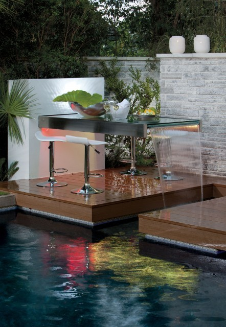Poolside outdoor dining area or bar seating with an unusual waterfall table (via Phil Kean Designs)