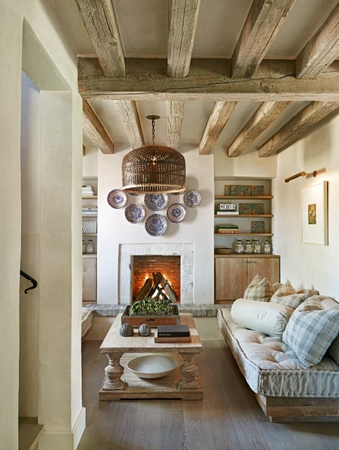 This rustic-style living room is simple yet beautiful, with pale wood trim, beams, and furnishings (via Don Ziebell)