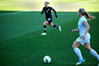 "Amy Rodriguez & Katie Hoyle USWNT v. New Zealand - Feb 11. Frisco, TX ————————————————- If I was going to have to sit next to a kid, the seven-year-old girl to my right was the best of tiny humans to be sitting next to for this match. She'd come all the way from Tampa as part of her birthday present, and even though she's seven she plays on a team with 10-year-olds. Despite the freezing cold, her attention never waned, she made intelligent observations and asked smart questions. Apart from that, she thought I was hilarious when I yelled out at a New Zealand defender to ""APOLOGIZE!"" after fouling Lauren Cheney. But perhaps most endearing was that she was screaming right along with me anytime A-Rod touched the ball or made her way down the left flank in front of us. I'd like to dedicate this photo to her."