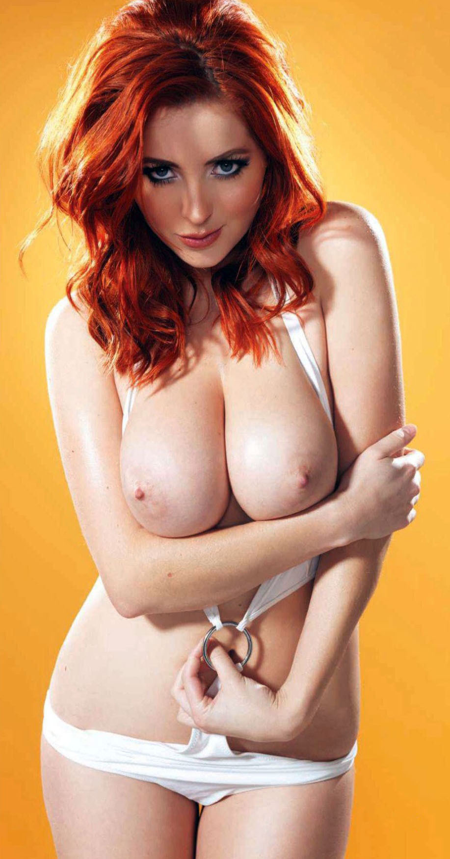 Sexy buxom redhead beauty with a naughty grin.