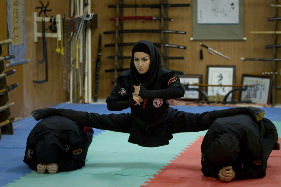 "popmuslim:  A Ninjutsu practitioner performs a split as members of various Ninjutsu schools showcase their skills to the media in a gym at Karaj, 45 km (28 miles) northwest of Tehran February 13, 2012. Currently about 3000 to 3500 women train in Ninjutsu in independently run clubs throughout Iran working under the supervision of the Ministry of Sports' Martial Arts Federation. Picture taken February 13, 2012.  via Iran's Female Ninjutsu Warriors My thought process, edited for clarity: Do any action movies include women like this? I think it would be a totally bad ass, would watch, 100%! The idea of this woman in a dramatic, fast-paced battle, like the Iranian version of Jackie Chan; kind of sickeningly awesome. I want so badly to see a westernized interpretation of this. This is subject matter that will likely not be approached by Hollywood in the near future, so I am entirely fine with an Iranian film with subtitles.  Me, Now: Sitting in bed, watching Iranian news programming on youtube, ""microblogging,"" wanting to be a ninja, pretty happy. Life's nice."