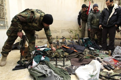 A Syrian soldier displays weapons seized from what officials say were  gunmen, during the tour of Arab monitors in Damascus countryside Harasta  January 26, 2012. Syrian authorities are holding ceasefire talks with  rebels who have seized some areas near Damascus, a local official said  on Thursday, in a sign that a 10-month-old revolt against President  Bashar al-Assad has crept close to the capital. REUTERS/Ahmed Jadallah