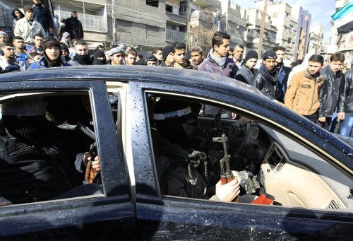 Syrian soldiers who have defected to join the Free Syrian Army, sit in a  car as they hold their rifles as they secure the area during a funeral  of a protester Mazen abou Dhahab in Saqba, January 27, 2012. REUTERS/  Ahmed Jadallah