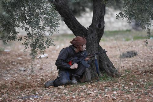 A Syrian rebel takes cover during an exchange of fire with army troops, unseen, in Idlib, Syria, Wednesday, Feb. 8, 2012. The European Union will impose harsher sanctions on Syria, a senior EU official said Wednesday, as Russia tried to broker talks between the vice president and the opposition to calm violence. Activists reported at least 50 killed in the regime's siege of the restive city of Homs. (AP Photo)