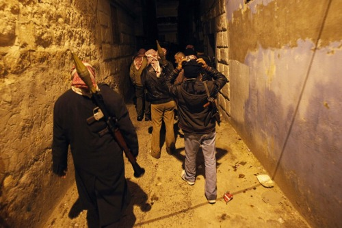 Syrian rebels walk in an alley in Idlib, Syria, Wednesday, Feb. 8, 2012. Activists say Syrian troops have continued shelling residential neighborhoods in the central city of Homs for the fifth straight day, killing scores of people. (AP Photo)