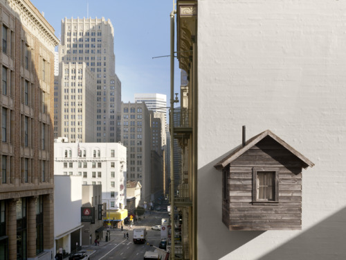 Tiny cabin spotted in downtown San Francisco.  Manifest Destiny! - created by artists Jenny Chapman and Mark A. Reigelman II. It currently resides on the side of the Hotel des Arts building in downtown San Francisco. Read more about it here.