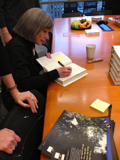 Anne Rice signing copies of The Wolf Gift for her admirers in the office.
