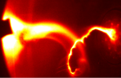"Stellar Explosions in the LabWhen an experiment consists of magnetism and plasma flying at 50 km/s you know it's got to be good. A recent experiment conducted at Caltech involves these and more. The experiment itself was conducted to better understand coronal mass ejections which form when magnetic fields ""snap"" and reconnect, expelling incredibly hot plasma in the process. Another phenomenon known as a Kink instability was also present. As the plasma is essentially 20,000 Kelvin gas of charged particles (with a current of 100,000 Amps) it generates a magnetic field as it moves. This magnetic field affects the charged particles in return, causing them to spiral and cork screw, which can be seen in this picture.The Kink instability also begets another instability known as the Rayleigh-Taylor instability (which is also what causes the tendrils on the inside of the Crab Nebula) which forms when a dense fluid attempts to move through a less dense fluid, in this case the dense plasma through the lower density vacuum that trails it, causing the ripples seen.Image"