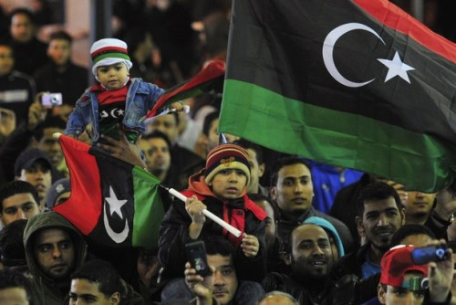 "Libya marks first anniversary of uprising Crowds in Tripoli and Benghazi begin impromptu celebrations amid heightened security and doubts about new rulers. Libyans have celebrated on the first anniversary of their uprising against Muammar Gaddafi, with the interim leader, Mustafa Abdel Jalil, pledging to act firmly against further instability. The former fighters, who toppled Gaddafi last year with NATO backing, set up fresh checkpoints in the capital, Tripoli, on Thursday, as well as in Benghazi, the eastern birthplace of the uprising, and the western port city of Misrata. The country's new rulers have not organised any official celebrations at a national level as a mark of respect for the thousands of people killed in the bloody conflict, which left about 15,000 people dead, according to the United Nations. But spontaneous celebrations began nationwide in cities and towns, led by residents of Benghazi, the city which first rose against Gaddafi and his 42-year-old regime. Protests broke out in Benghazi on February 15 after the arrest of human rights lawyer Fathi Terbil, but the first widely recognised ""Day of Rage"" came on February 17. Pictured: People with with post-revolutionary Libyan flags mark the one year anniversary of the revolutionary uprising against Muammar Gaddafi. The flag which was used when Libya gained independence from Italy in 1951, was used as a symbol of resistance against Gaddafi. Esam Omran Al-Fetori/Reuters"