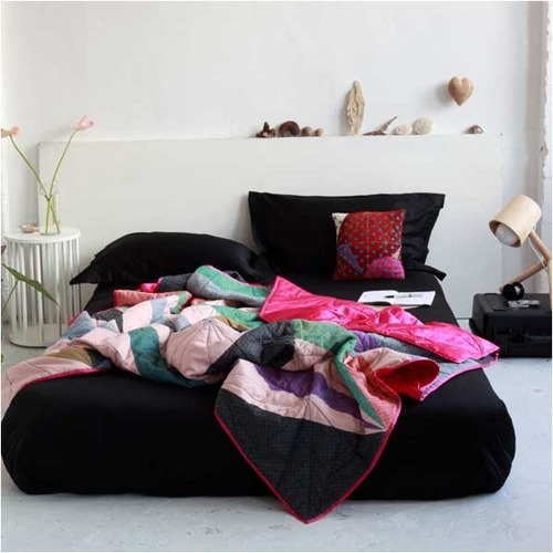 ruemag:  Black bedding, colorful quilt, white walls…a striking combo!  source.