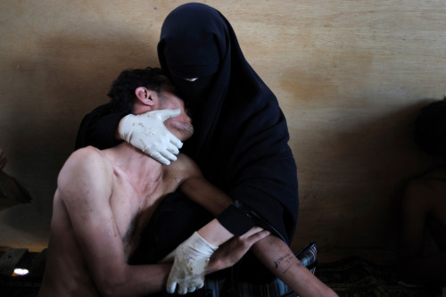 2012 World Press Photo of the Year: A woman holds a wounded relative during protests against President Saleh in Sanaa, Yemen, Oct. 15, 2011. (Samuel Aranda/The New York Times)