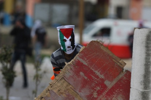 simply-war:  Feb. 15, 2012. A Palestinian youth masked with the colors of his national flag hides behind a makeshift barricade during clashes with Israeli soldiers at the entrance of the Israeli Ofer Prison near Ramallah in the occupied West Bank.Photography by; Abbas Momani.