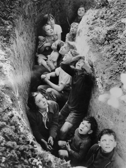 lapetitecole:  British children huddled in a makeshift bomb shelter experience a range of emotions as they endure an attack by Hitler's Luftwaffe.