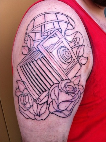 So this is my boyfriend's tattoo. It is an old accordion style camera because he loves photography and film making. He hopes to pursue a career in film and do that for the rest of his life. It is a great passion of his. :) This was taken right after the lines were finished and he is going back in to get finished really soon!  It was done at the Hart and Huntington in Orlando, Florida's City Walk by Isaac Bills.