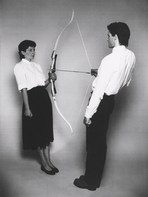 "Abramovic, Marina; Ulay  Rest Energy, 1980  c-type print, 2006 65.2"" x 49.2""      «Rest Energy» Standing across from one another in slated position.  Looking each other in the eye. I hold a bow and Ulay holds the string  with the arrow pointing directly to my heart. Microphones attached to  both hearts recording the increasing number of heart beats."