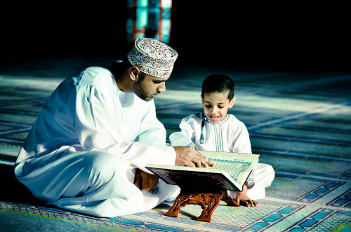 poeticislam:    A man teaching his son to read Quran in one of the mosques in Muscat, Oman. Taken by Hussain Al Bahrani