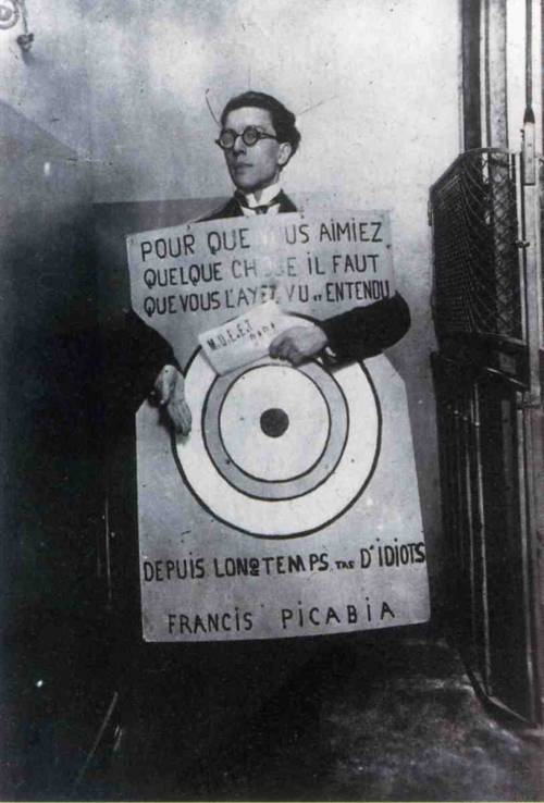 rhea137:  André Breton at a Dada festival in Paris, March 27, 1920, wearing a slogan by Francis Picabia: In order to love something you need to have seen and heard it for a long time bunch of idiots