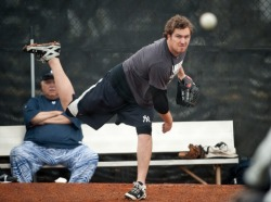 inothernews:  FOREGROUND:  Yankees pitcher Phil Hughes throwing in the bullpen as New York's pitchers and catchers report for their first day of spring training Sunday. BACKGROUND:  Holy shit, those fucking pants.  (Photo via the New York Daily News)