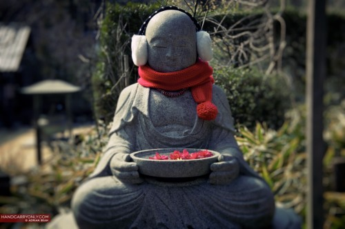 Jizo keeping warm | Kamakura, Japan 2012 Jizō, or Ojizō-sama as he is respectfully known, is one of the most loved of all Japanese divinities. His statues are a common sight, especially by roadsides and in graveyards. Traditionally, he is seen as the guardian of children, particularly children who died before their parents. Since the 1980s, he has been worshiped as the guardian of the souls of mizuko, the souls of stillborn, miscarried or aborted fetuses, in the ritual of mizuko kuyō (水子供養, lit. offering to water children). In Japanese mythology, it is said that the souls of children who die before their parents are unable to cross the mythical Sanzu River on their way to the afterlife because they have not had the chance to accumulate enough good deeds and because they have made the parents suffer. It is believed that Jizō saves these souls from having to pile stones eternally on the bank of the river as penance, by hiding them from demons in his robe, and letting them hear mantras. Jizō statues are sometimes accompanied by a little pile of stones and pebbles, put there by people in the hope that it would shorten the time children have to suffer in the underworld. (The act is derived from the tradition of building stupas as an act of merit-making.) The statues can sometimes be seen wearing tiny children's clothing or bibs, or with toys, put there by grieving parents to help their lost ones and hoping that Jizō would specially protect them. Sometimes the offerings are put there by parents to thank Jizō for saving their children from a serious illness. Jizō's features are commonly made more babylike to resemble the children he protects. As he is seen as the saviour of souls who have to suffer in the underworld, his statues are common in cemeteries. He is also believed to be one of the protective deities of travelers, the dōsojin, and roadside statues of Jizō are a common sight in Japan. Firefighters are also believed to be under the protection of Jizō. (info from Wikipedia)     View my other photos of Japan!