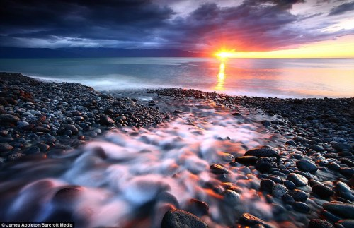 The sun cuts under a close storm system at sunset over the bay near Husavik, northern Iceland.  Photo by James Appleton