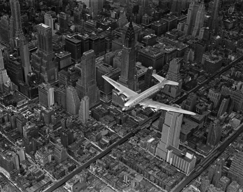 Margaret Bourke-White Aerial view of a DC-4 passenger plane flying over midtown Manhattan.  1939