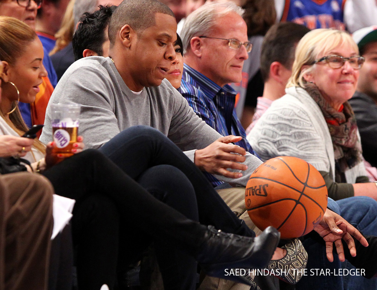 Jay-Z attempts to spin a basketball on the tip of Beyonce's high heel shoe during a time-out, as the New York Knicks play against the New Jersey Nets Monday February 20, 2012 at Madison Square Garden.