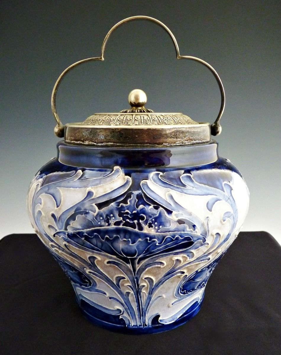 Biscuit jar designed by William Moorcroft while working for  James MacIntyre and Co. Ltd.  This is Florian Ware which was made just a  short time.  This particular piece; based on registration mark was  produced between 1900-1906.       WILLIAM MOORCROFT FLORIAN WARE POPPY  VASE  This  Florian Ware vase was designed by William Moorcroft during his time at  the James MacIntyre & Co pottery here