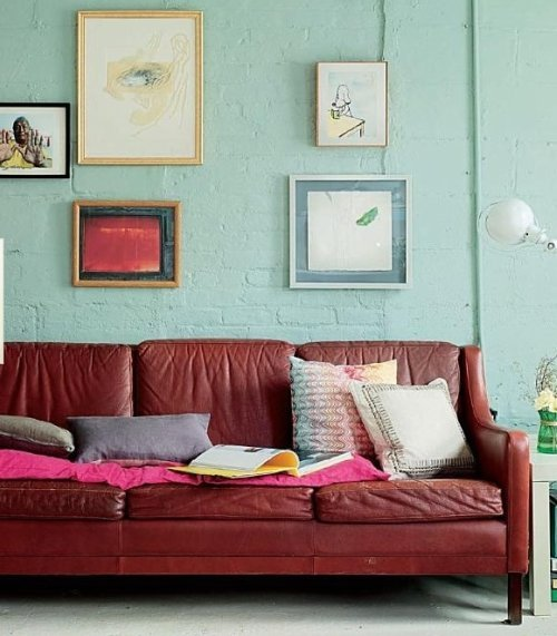 Minty green wall + vintage rhubarb sofa = love. Great haphazard placement with the art on the wall as well!  source.