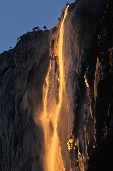 Yosemite waterfall, seemingly on fire. wfplnews:  If you head to Yosemite National Park this time of year and stop by Horsetail Fall at just the right time, you might see something spectacular: As the sun sinks low in the sky, the waterfall glows with streaks of gold and yellow — and it looks just like molten lava. Photographers like Michael Frye flock to the park every February to try to capture the phenomenon. Frye, author of The Photographer's Guide to Yosemite, describes the sight to NPR's Audie Cornish. Listen to the interview. (via From Waterfall To Lavafall: Yosemite's Fleeting Phenomenon : The Picture Show : NPR)