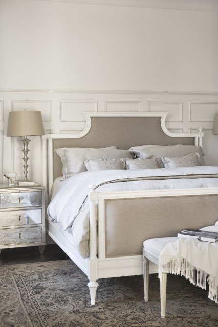 Understated and elegant, this bedroom combines modern and antique furniture with painted wainscoting on the walls (via Linda McDougald Design)