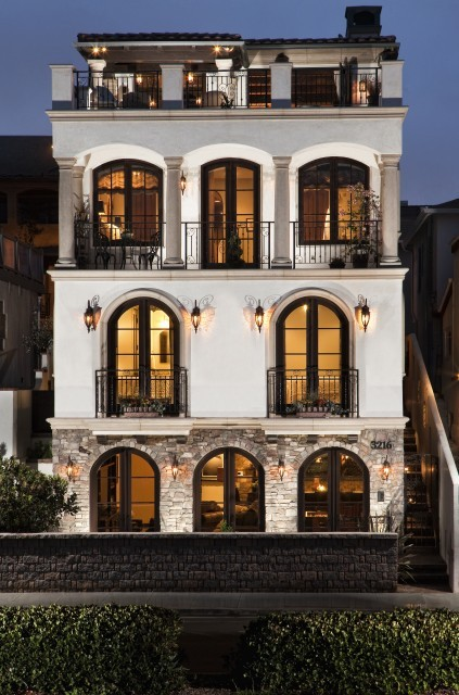 Love the abundance of arched windows on this Mediterranean-style villa (via David Watson, Architect)