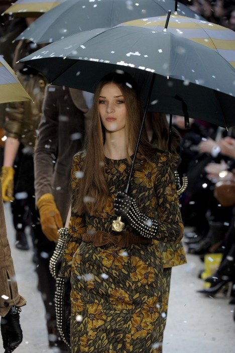 "Rain in Burberry London Fashion Week AW 2012-2013 Burberry Prorsum is one of my favorite fashion show during London Fashion Week. Burberry creative director Christopher Bailey combined country and town styles for an elegant collection. He created cropped tailored bomber jackets, draped hem blanket skirts and sculptural dress shirts featured prominently.  He also created pencil skirts with large bellow pockets, peplum skirts, and double-breasted jackets. The trademark for the Burberry is their raincoat, so Burberry used rain at the end of the show when all of the models walked together carrying brightly coloured umbrellas. The rain is made of silver paper. There is also rain at outside of the transparent marquee in which event was hosted. ""I think Burberry is a quintessentially British brand that Christopher has totally reinvented and made young and hip and fun and made an incredible global success,""Anna Wintour said."