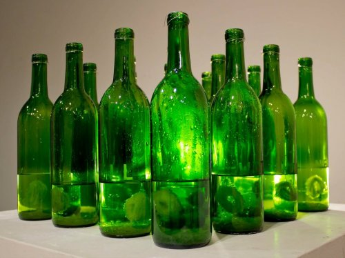 "Kill Them With Kindness by Aubrey Davis Sculpture 2012 Wine bottles, wire, borax, water, amour etch, pipe cleaners.  This sculpture is a self portrait.  I grew crystals (or attempted to) in each bottle.  I experimented with multiple different formulas and the Borax/water solution seemed to work out the best.  I formed little spheres out of pipe cleaners and suspended them by wires hooked to the rim of the bottle.  I then etched the title ""kill them with kindness"" on 5 out of the 16 bottles."