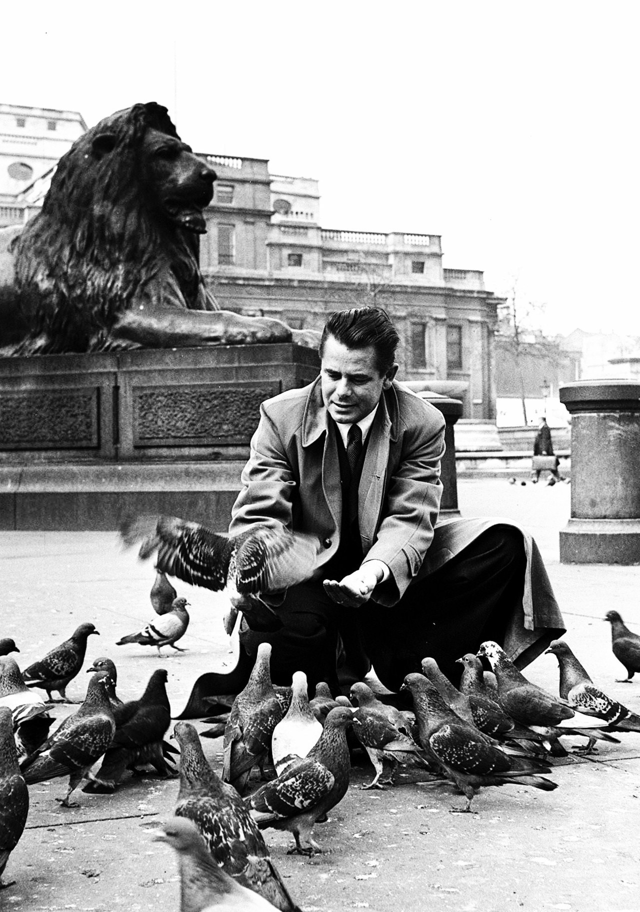 Glenn Ford feeding pigeons in Trafalgar Square in London, England, 1951.