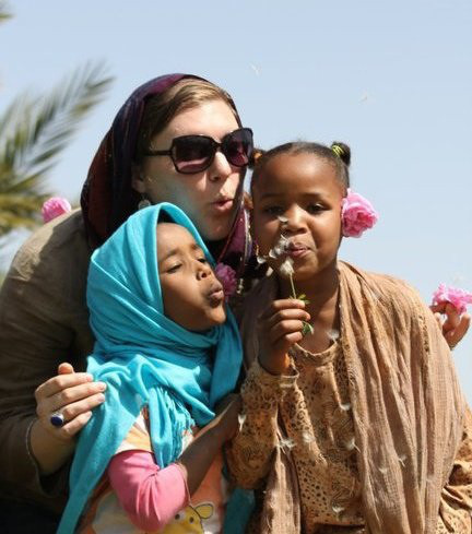 In the photo, I was teaching two of my host sisters, Samira and Hafsa, about how in America we make wishes on dandelions. We live in the Sahara desert but near an Oasis. Here the children know every plant, herb and even weed that grows. They always want me to eat some strange seed, or smell a weird plant. Now they know another use for dandelions! Photo taken by fellow Volunteer, Jo Troyer.  Peace Corps Youth Development Volunteer	Rachel Rubinski