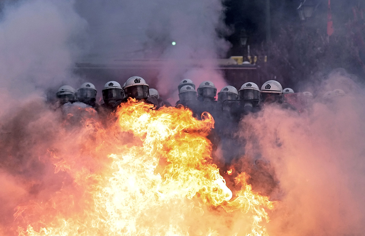 From Athens in Flames, one of 36 photos. In this image, riot policemen stand guard as petrol bombs explode in front of them during clashes with protesters outside the Greek parliament in Athens, Greece, on February 12, 2012. Greek police fired tear gas at petrol bomb-throwing protesters outside parliament, where tens of thousands had massed in a rally against austerity plans being debated by lawmakers. (Aris Messinis/AFP/Getty Images)