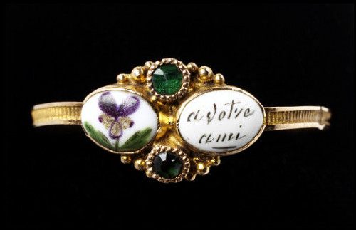 Gold ring set with two green glass stones and enamelled plaques decorated with pansies and the inscription 'A votre ami'. 1819-1838. This ring was a romantic present from a man to his love. The French word 'pensées' means both pansies, as painted on the bezel of this ring, and 'thoughts'. In this case the pansies stand for 'pensez', meaning 'think'. The flowers and words taken together read 'Pensez à votre ami', 'think of your friend'. The lover hoped that his love would wear the ring and think of him.
