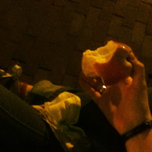Sitting on a wall, eating an apple. Content.
