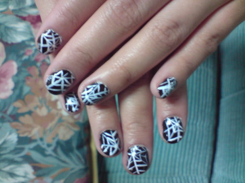 Spider Webs Materials: - Black Base Coat - White Fine Line How To:Apply black base coat and wait till it dries, two coats would be preferable. With a white fine line, place a random dot designating the middle of the web and starting from that dot, spread at least 5-6 lines outwards. In between those lines, you're gonna want to go in a zig-zag fashion to have the appearance of a spider web. Finish it off with a top coat (but i didn't in this case DX). Good luck and Have fun <3