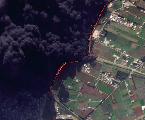 "BORDERLAND   This satellite image shows a pipeline fire in Homs, Syria. The pipeline,  which runs through the rebel-held neighbourhood of Baba Amr, had been  shelled by regime troops for the previous 12 days, according to two  activist groups, the Local Coordination Committees and the Britain-based  Syrian Observatory for Human Rights. The state news agency, SANA,  blamed ""armed terrorists"" for the pipeline attack.  (Photo: Digital Globe / AP via the Telegraph)"