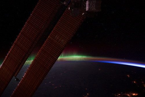 "spacettf:  A 'Slice' of Daybreak (NASA, International Space Station, 02/04/12) by NASA's Marshall Space Flight Center on Flickr. Via Flickr: This nighttime view of Earth's horizon and scattered city lights was photographed by one of the Expedition 30 crew members aboard the International Space Station. Activity of Aurora Borealis appears from behind one of the orbital outpost's solar array panels, then fades into an area where Earth's limb is visible and finally a small ""slice"" of daybreak appears at right.  Image credit: NASA"