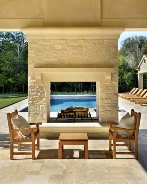 Two-way outdoor fireplace with a living area on one side and a pool on the other (via Bernard Ande Photography)