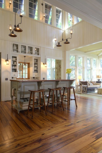 An open, light, and airy rustic kitchen with painted beadboard walls, wood floors, and clerestory windows (via Group 3)