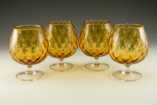 "(via Retro Art Glass: Set of Retro Italian Blown Glass Brandy Snifters) Rare set of blown optic glass brandy snifter balloons.  Each hold 7 ounces (with 1"" lip-service). Perfect for brandy, but great for fancy mixed cocktails too. Not often seen in this size.  These are made to drink from, rather than the oversize optic snifter balloons which were made to be used as vases.  Especially hard to find as a set. All in like-new condition.  Hand-made in Italy, circa 1950s. Blown from a diamond pillow optic mold in golden amber glass.  The colorless foot and stem were formed separately and applied.  Stand 4 1/8"" tall. Perfect for the retro modern bar.  Unique Italian bar glass. See it at:"
